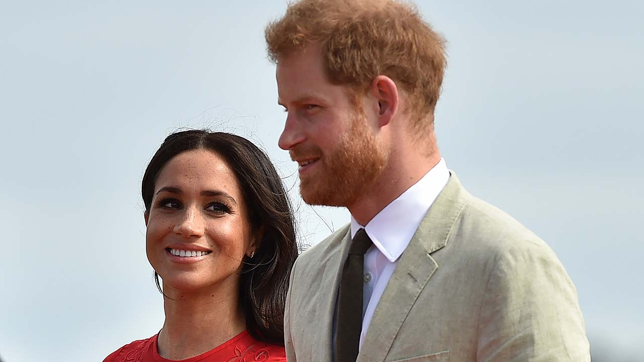 A close-up shot of Meghan Markle in a red dress and Prince Harry in a suit