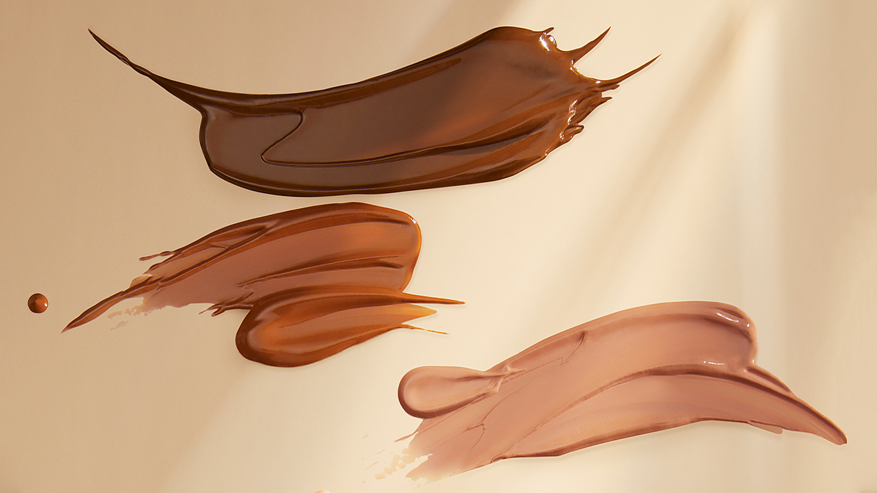 Swatched of tinted moisturizers on beige background.