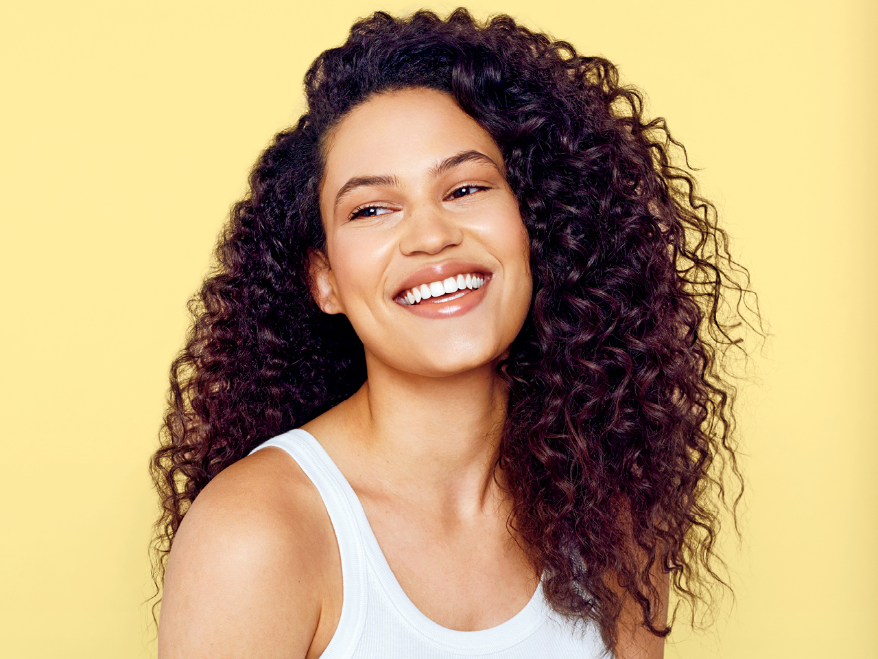 A model with curly hair against a yellow background to illustrate tips on how to air-dry hair.