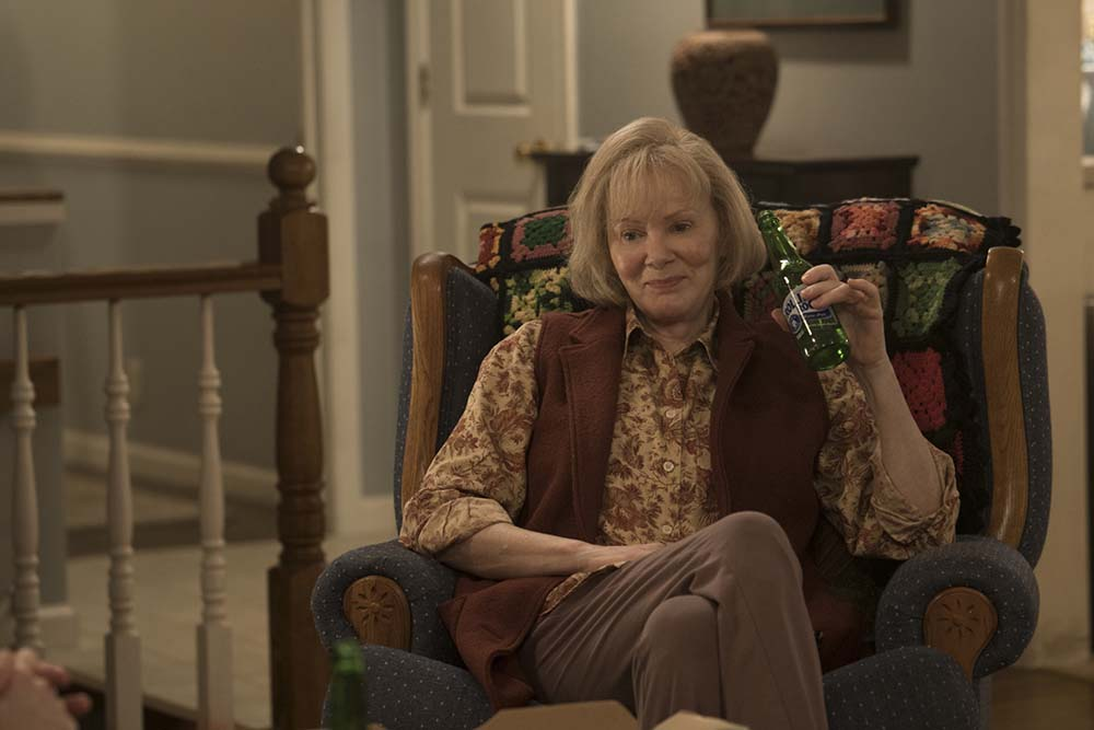 Jean Smart sitting in an easy chair holding a beer