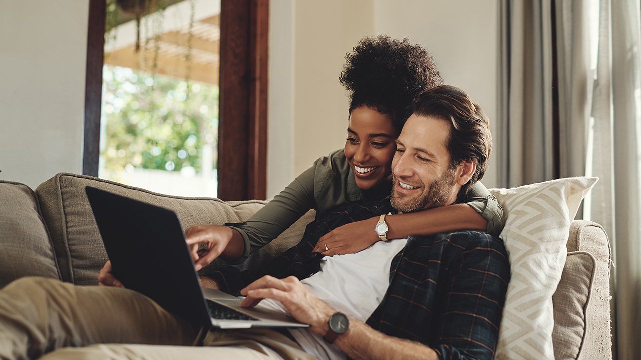 Shot of a happy young couple using a laptop while relaxing on a couch