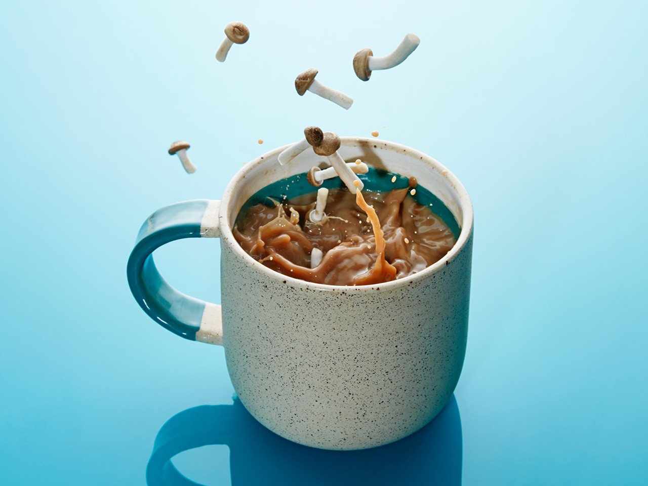 Mushrooms dropping into a mug of water against a blue background