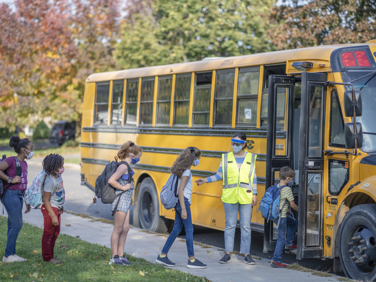 Students getting on the bus wearing protective face coverings due to COVID-19 regulations.
