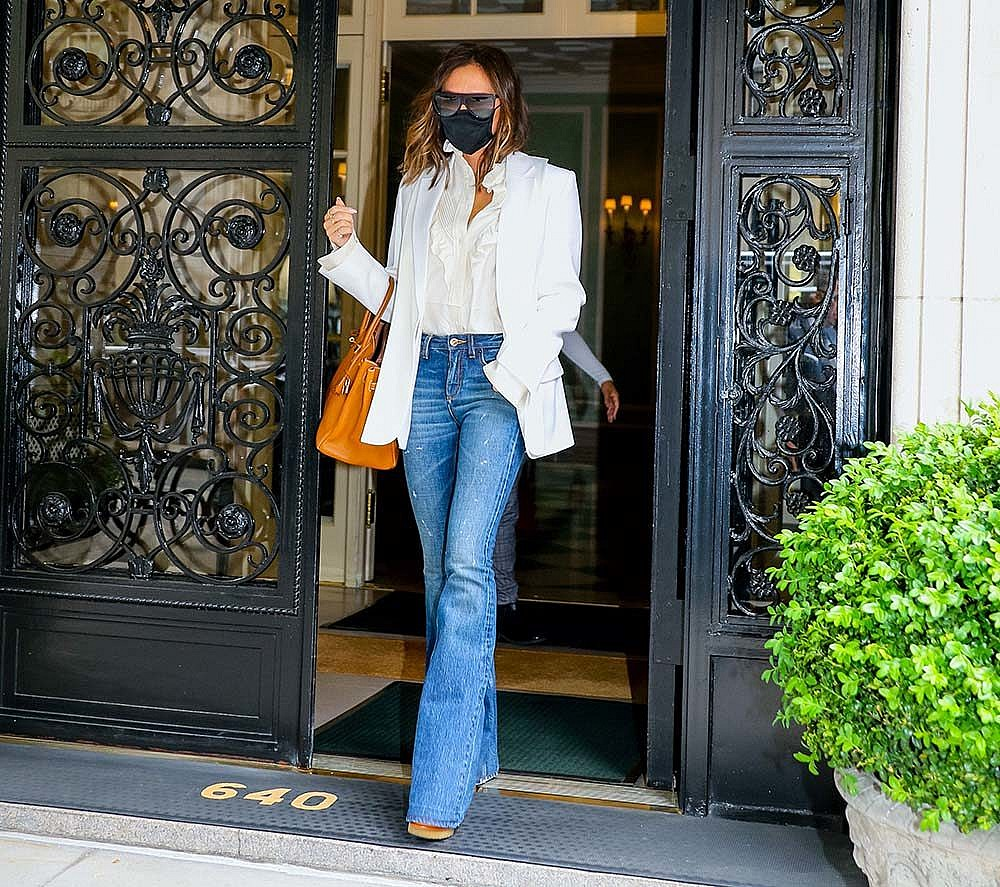 Victoria Beckham in New York City in a white blouse, flare jeans, a white blazer, carrying a tan Hermes birkin