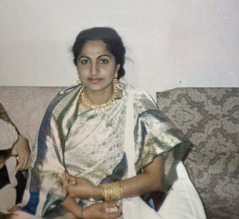 The author's mother, wearing a gold necklace, earrings and bracelets, in an old photo