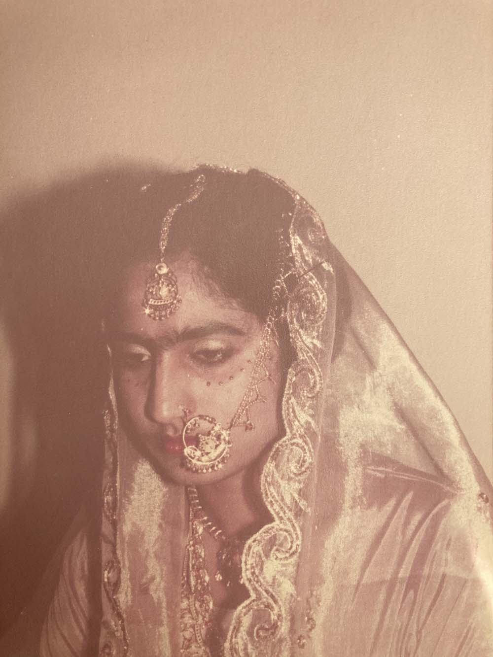 An old photo of the author's mother at a wedding, wearing red and gold jewellery, including nath (a nose ring and chain)