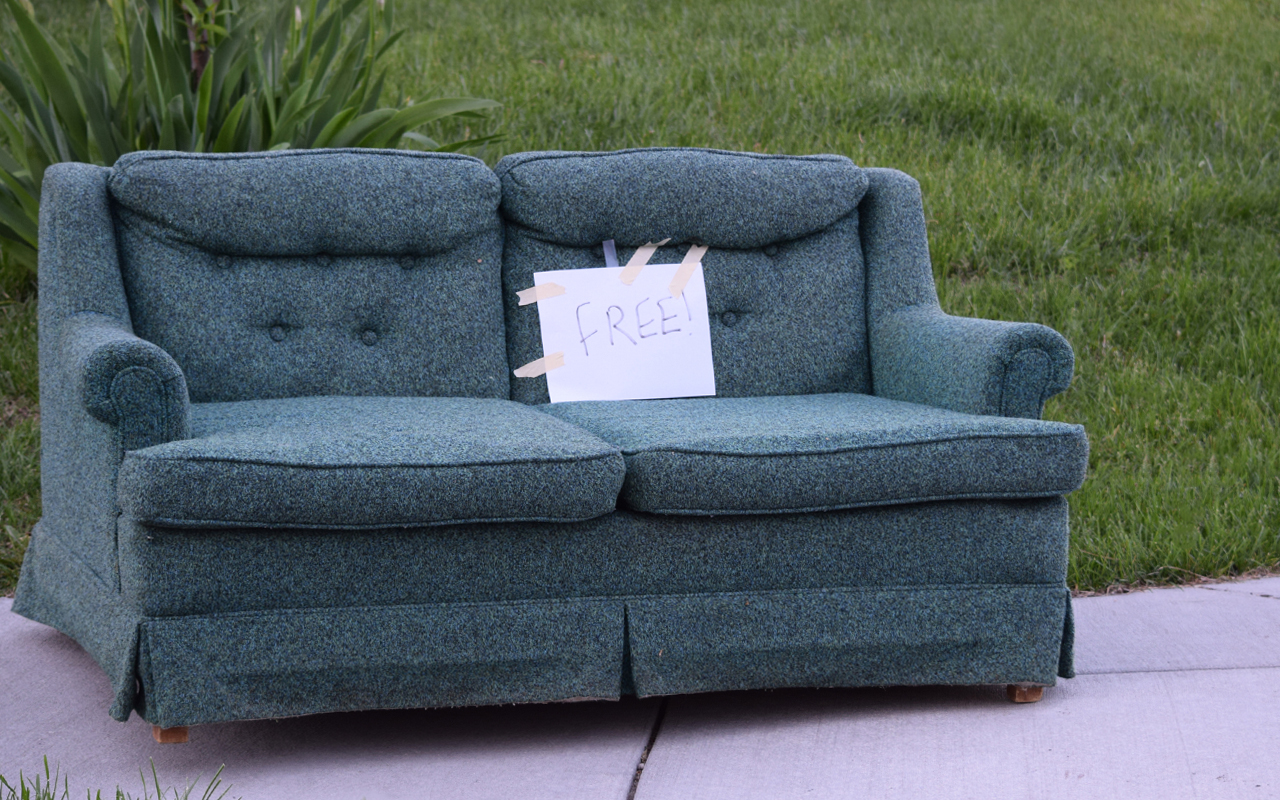 """A teal couch with a sign marked """"free"""" to illustrate an article on curbing and how to furnish your home for free."""