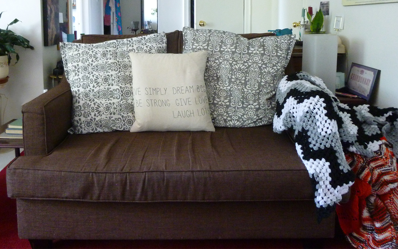 A brown couch with pillows in an apartment furnished for free through curbing.