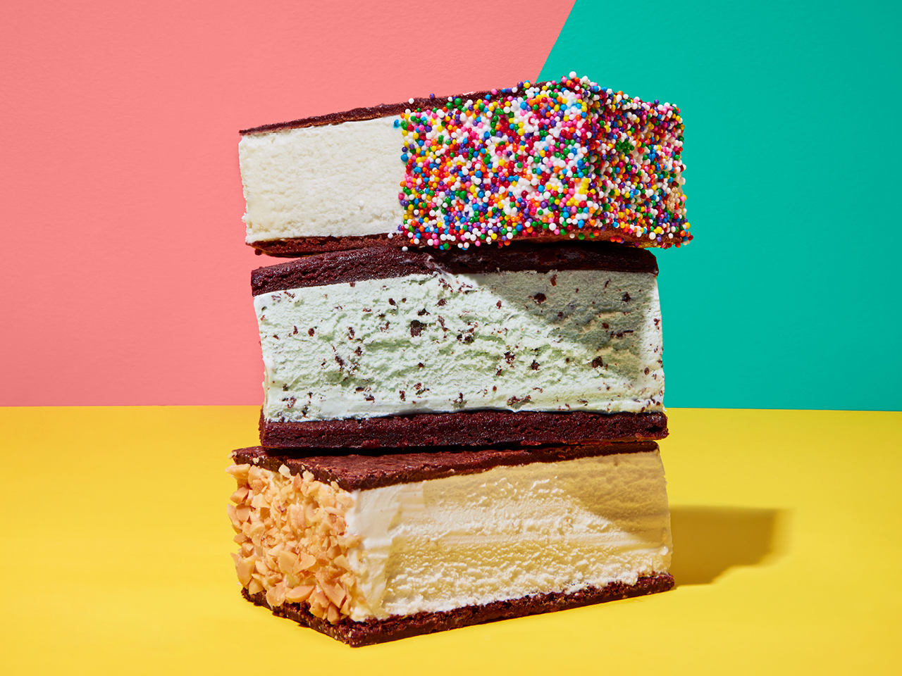 A stack of ice cream sandwiches, with different types of ice cream, on chocolate wafers; one is dipped into sprinkles, one into coconut