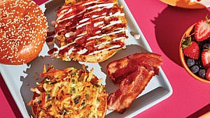 An okonomiyaki breakfast sandwich on a plate with bacon, with a side bowl of berries and a glass of orange juice