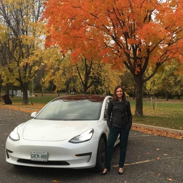 Laura Mason stands beside her white Tesla Model 3 Standard Range Plus in front of a fall tree backdrop