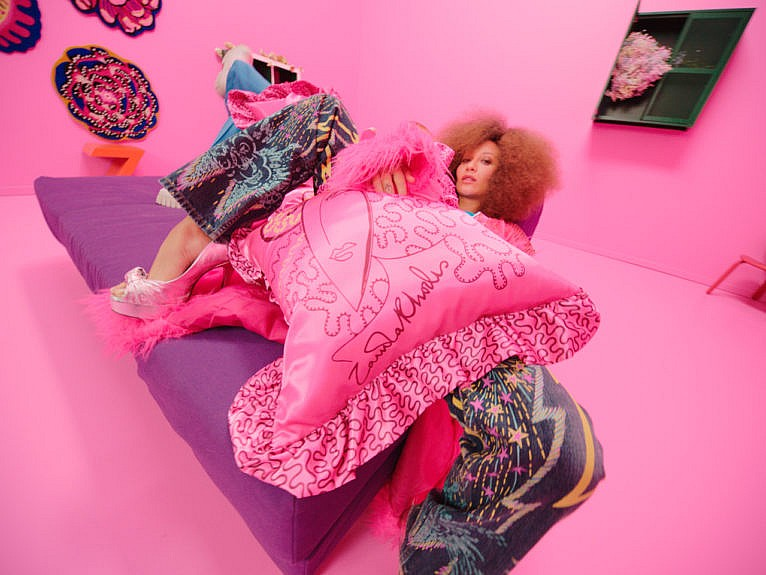 Woman sits in a pink room surrounded by colourful furniture, looks at camera.