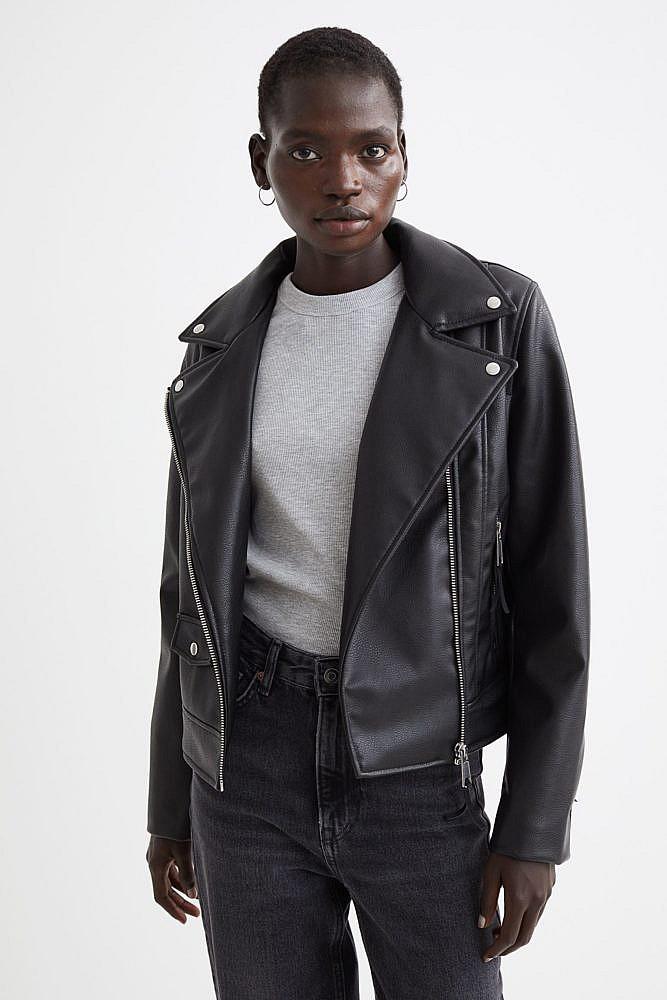 A model in a black faux leather biker jacket, grey t-shirt, black jeans and hoop earrings