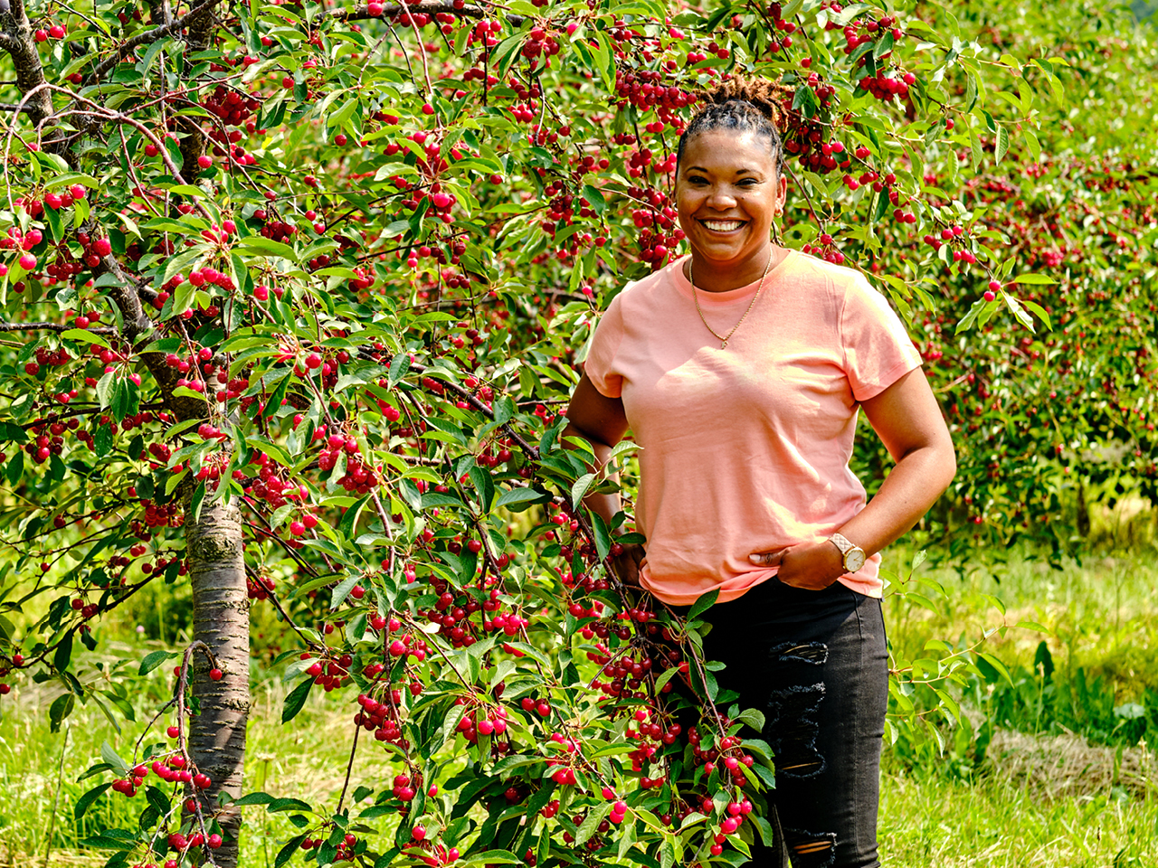 Felena Pereira stands beside a tree with fruit