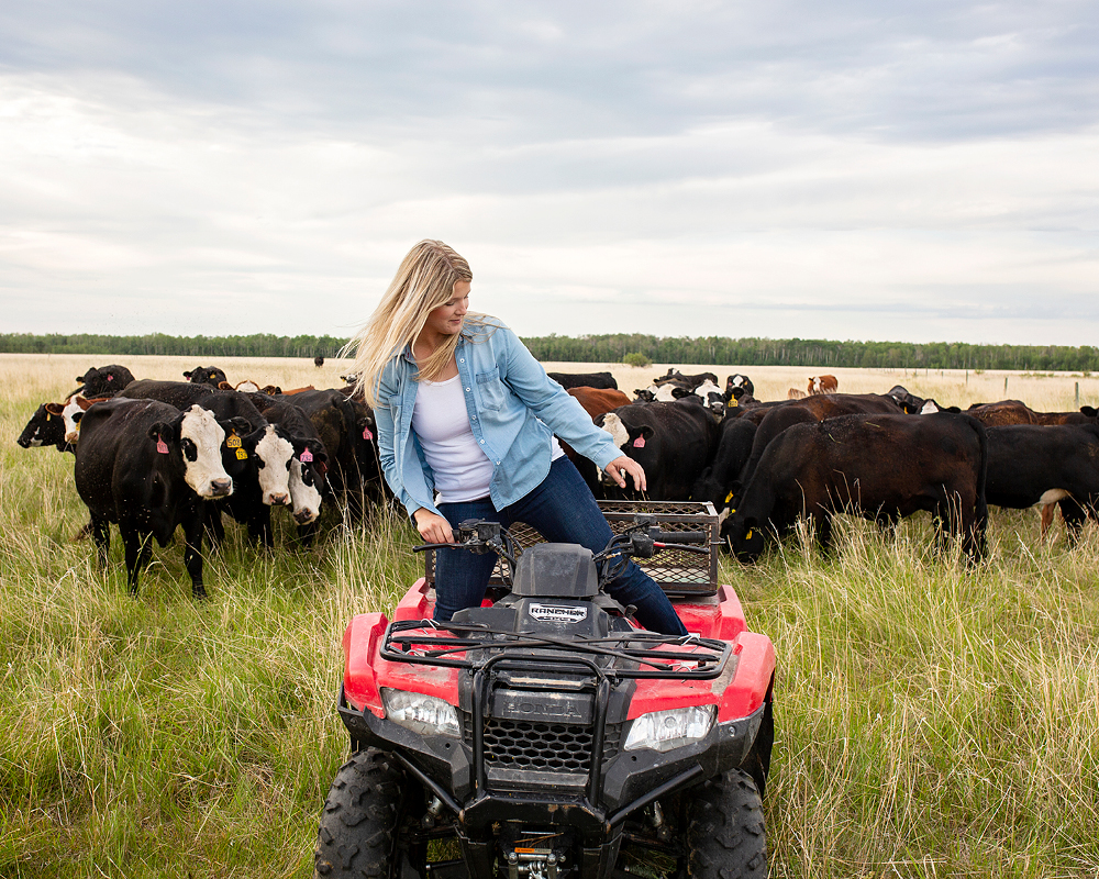 Kristine Tapley poses on an ATV, with a group of grown cows behind her