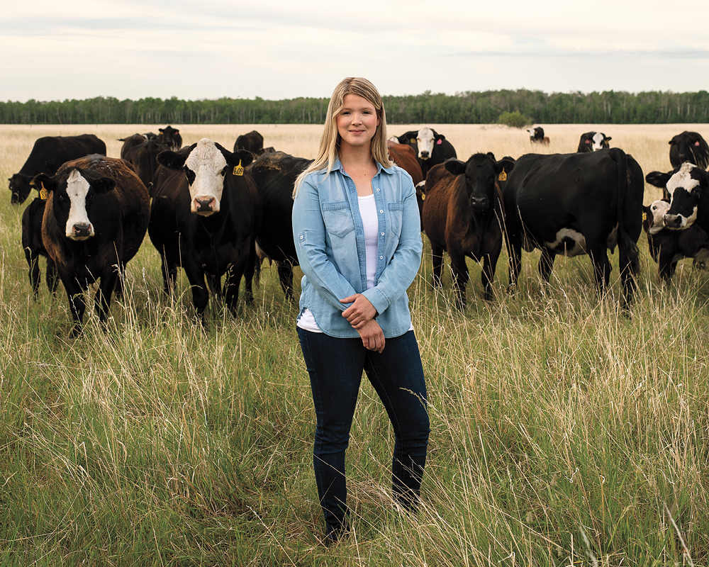 Kristine Tapley stands in grass, with a group of brown cows behind her
