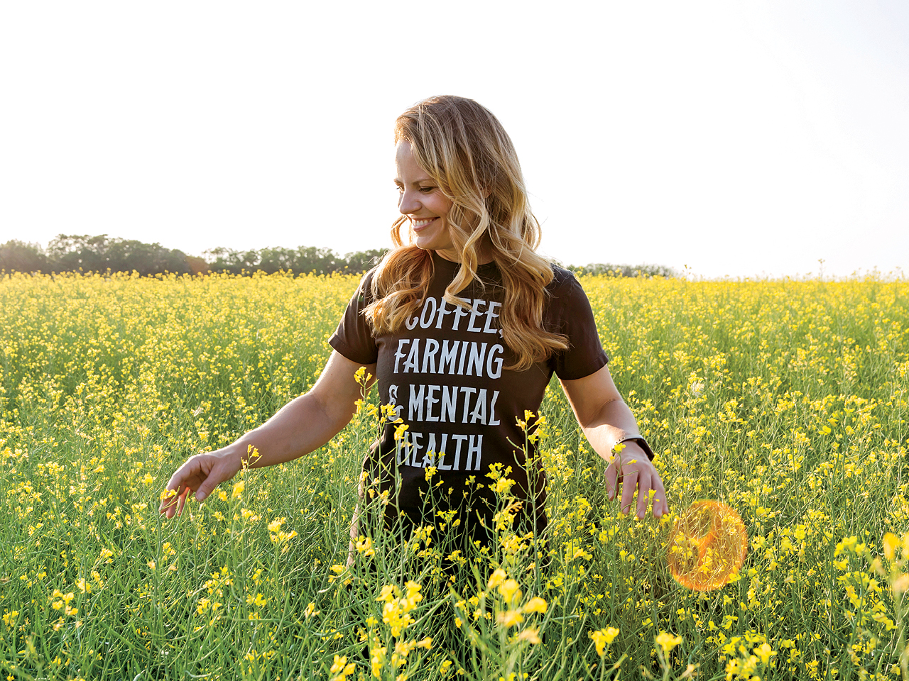 Lesley Kelly stands in a field of flowers, her shirt says 'Coffee, Farming and Mental Health'