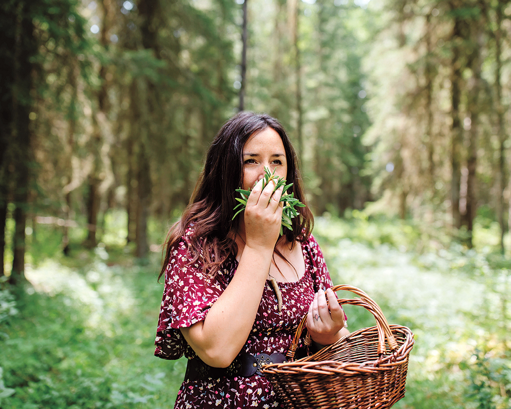 Tiffany Traverse stands in a forest, holding a wicker basket in her left hand and a handful of plants up to her nose in her right hand