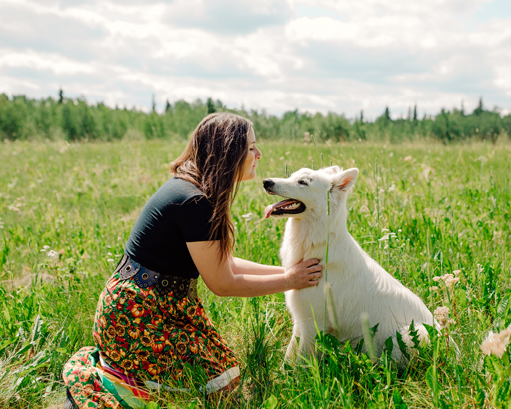 Tiffany Traverse sits in a field and faces a white dog that sits next to her