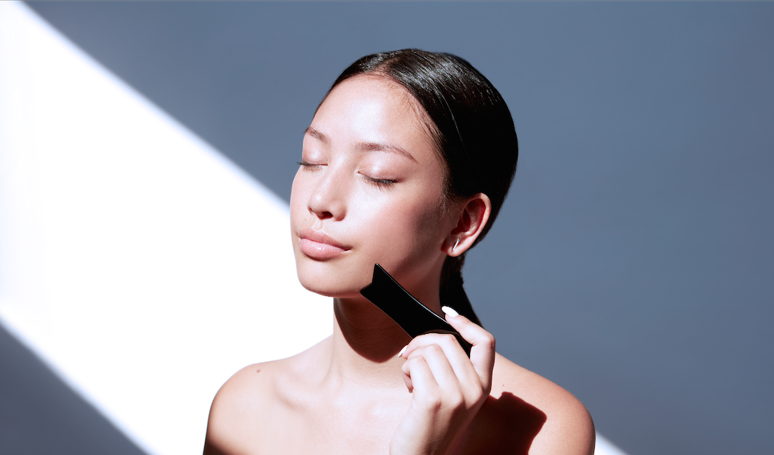 A woman using a gua sha tool against a bright background.