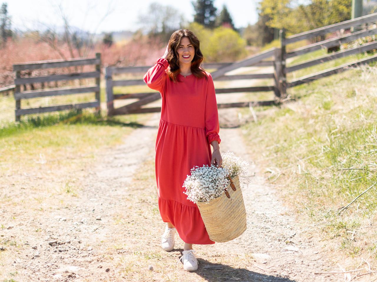 Jillian Harris wearing a red dress in a field to illustrate an article about Joe Fresh x Jillian Harris collection 2021.