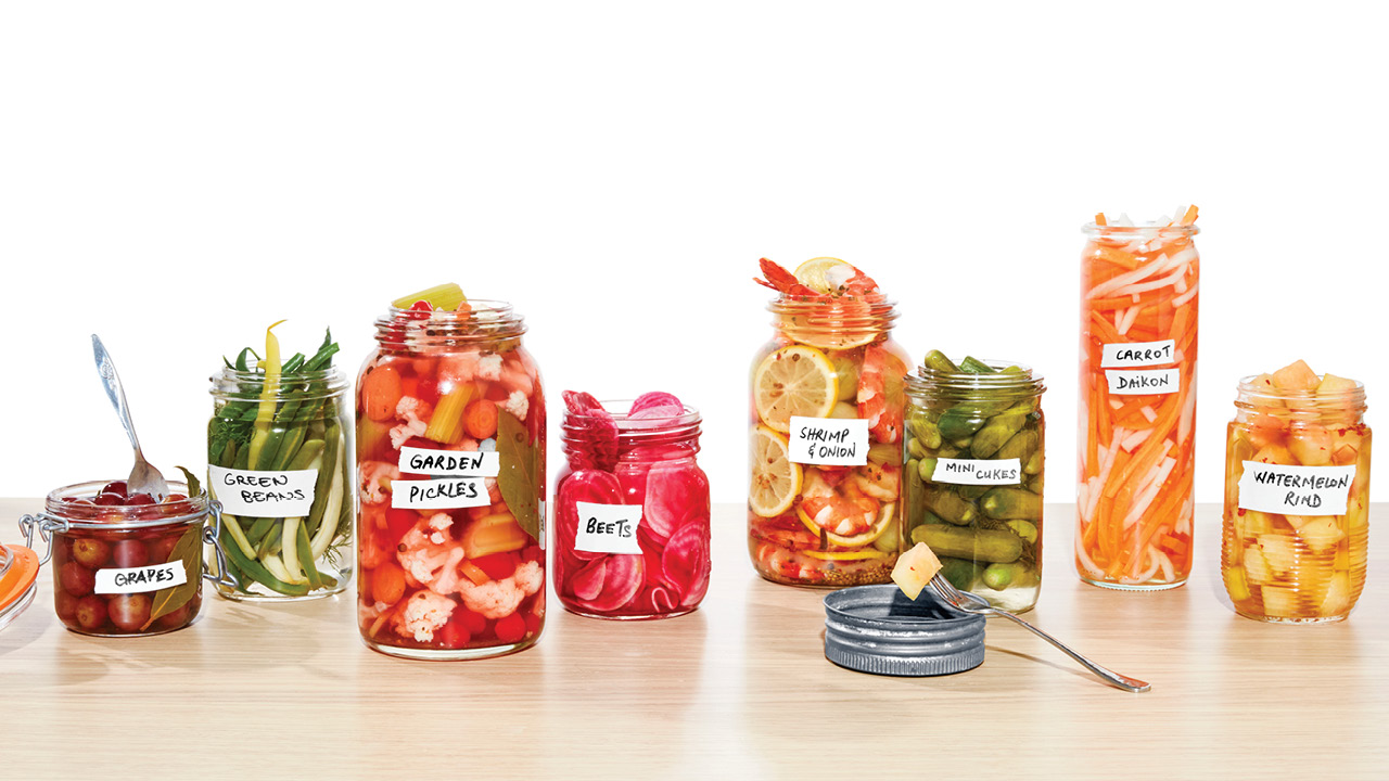 Eight jars of various pickle recipes sit next to one another on a table.
