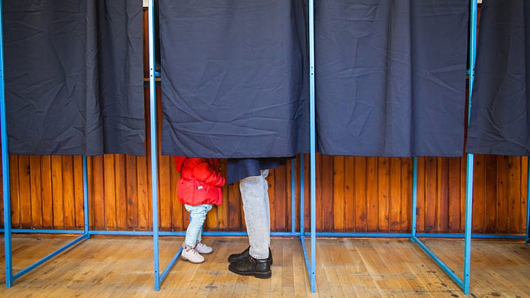A photo of a curtained voting booth, with the feet of a small child in a red coat and a parent sticking out under the curtain
